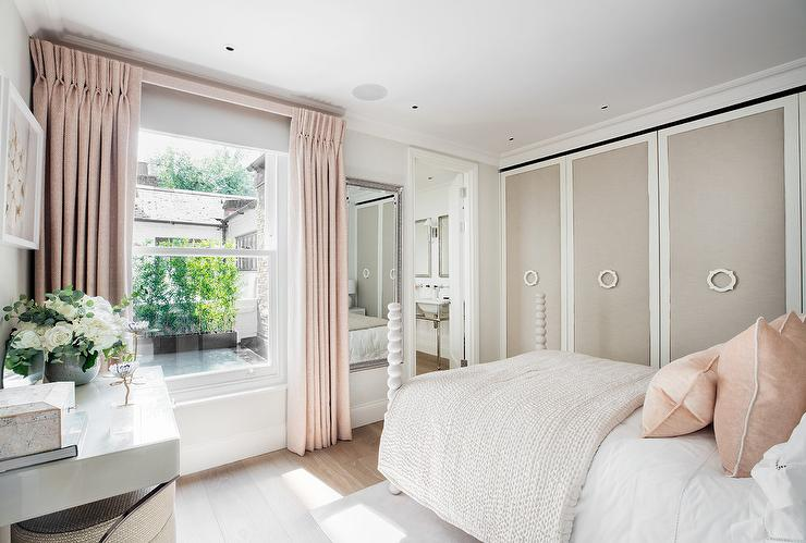 lovely pink and dove gray bedroom is furnished with a white 4 poster bed dressed in white bedding topped with blush pink linen pillows