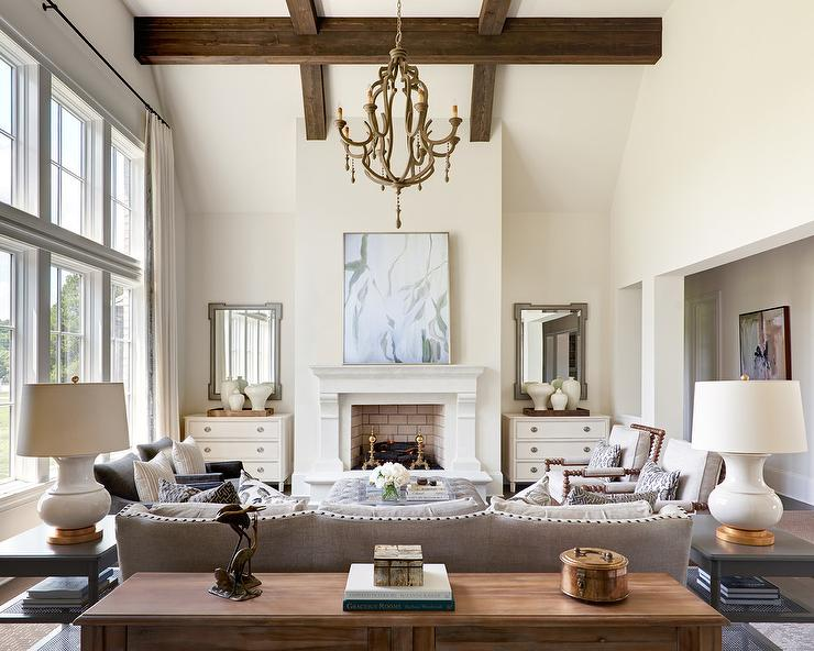 A Wooden Chandelier Hangs From A Tall Living Room Accented With Wood Beams  Over A Light Gray Linen Sofa Flanked By Black End Tables Topped With White  And ... Part 62