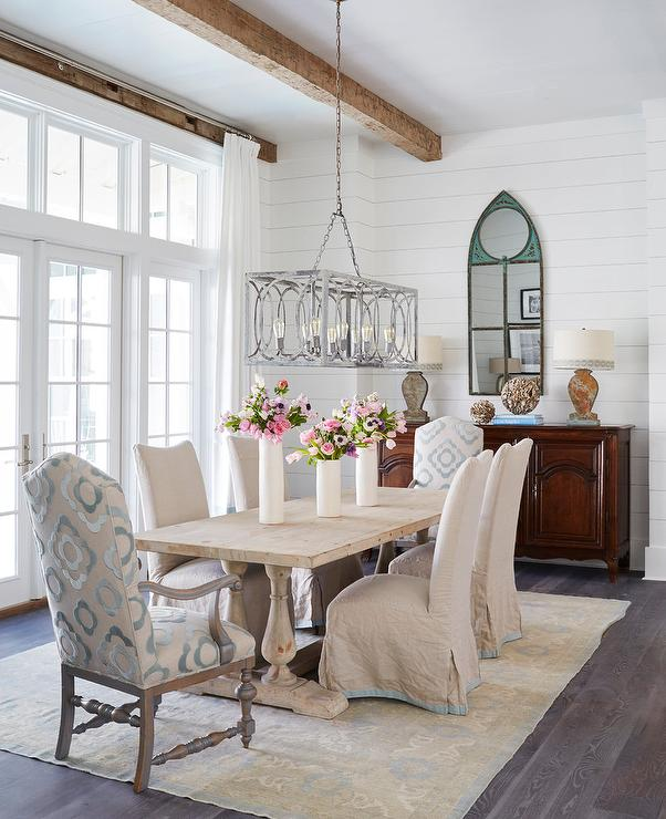 Beautiful Cottage Dining Room Features A Blond Wood French Table Placed On Yellow And Blue Persian Rug Seating Beige Slipcovered Chairs