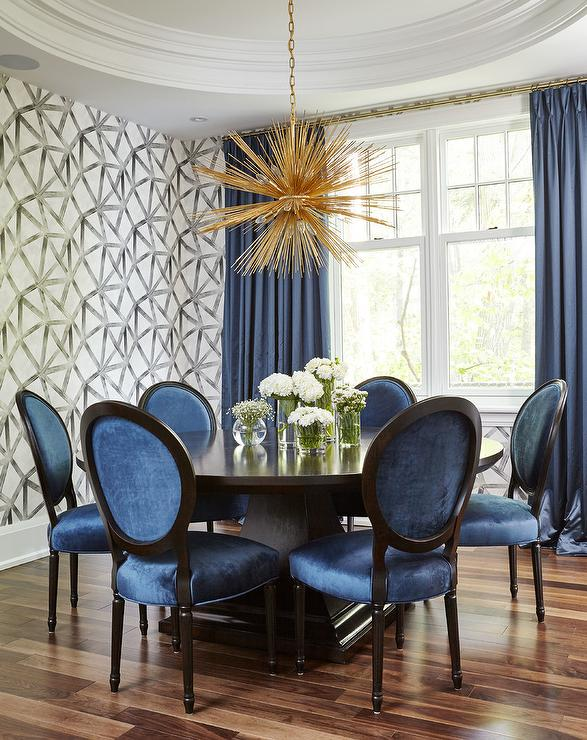 Contemporary dining room boasts a brass urchin chandelier hung over a round dark stained dining table surrounded by 6 oval back blue velvet dining chairs. & Oval Back Blue Velvet Dining Chairs Design Ideas