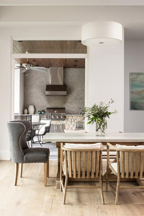 a stone and wood dining table is flanked by wood slated dining chairs and seats dark gray wingback head chairs lit by a white drum light pendant