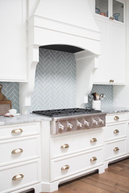 wood french hood finished with white corbels is mounted to blue herringbone backsplash tiles beneath white cabinets accented with satin nickel knobs and