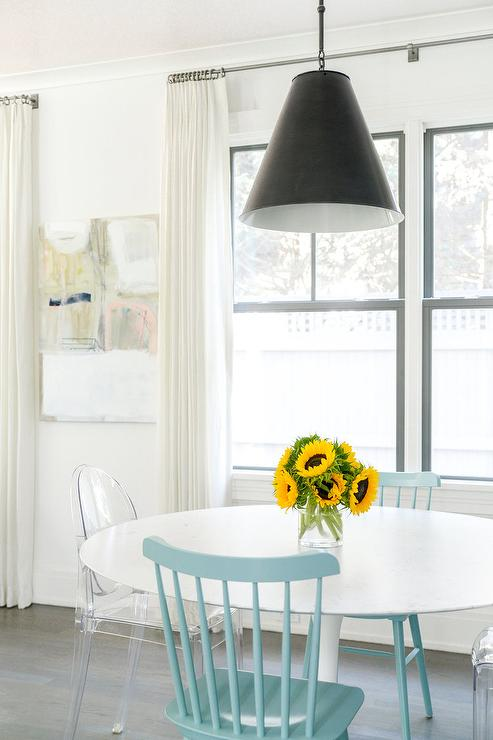 Black spindle beside lamp design ideas a goodman hanging lamp hangs over a saarinen oval dining table seating kartell victoria chairs and turquoise blue wood spindle dining chairs mozeypictures Image collections