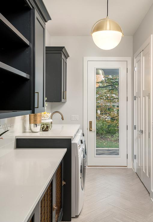 Black Laundry Room Cabinets With White Quartz Countertops And Gray  Herringbone Tiles Create A Well Balanced Design In A Laundry Room With A  Glass Door ...