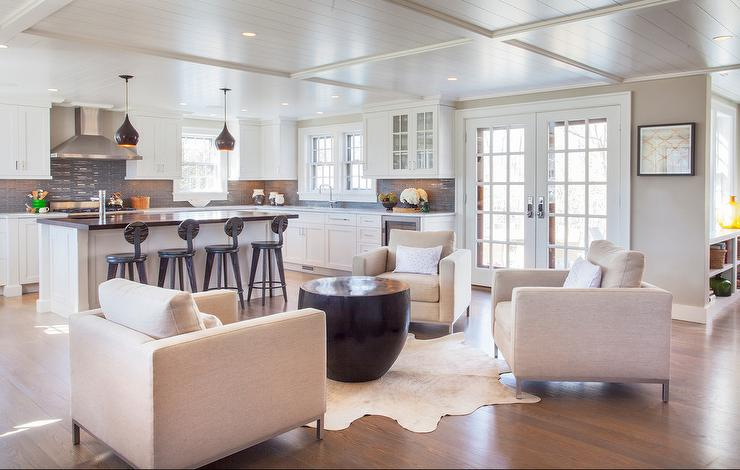 colorful chairs for living room. In front of a beautifully designed kitchen  three ivory club chairs surround black coffee table placed on an cowhide rug beneath shiplap ceiling Living Room design decor photos pictures ideas inspiration