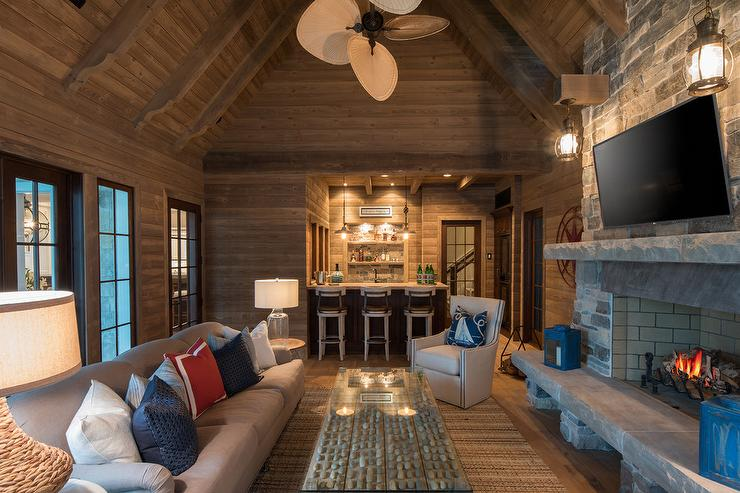 Stunning Cabin Style Living Room Is Fitted With Plank Walls And A Vaulted  Plank Ceiling And Features A Long Gray Sofa Accented With Blue And Red  Pillows.