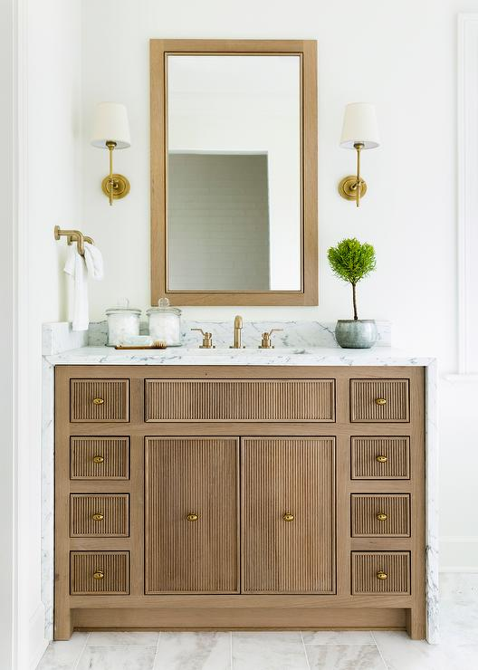 Beige Reeded Washstand With Antique Brass Sconces Transitional Bathroom