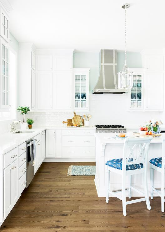 A teal fringe runner sits in front of a stainless steel range fixed between  white drawers adorned with polished nickel pulls and a white marble  countertop.