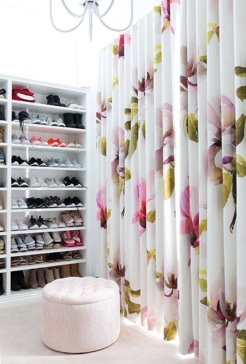 Pink And Green Curtains Hang In A Closet Behind Light Tufted Storage Ottoman Placed On Cream Carpeting Front Of Built Shoe Shelves Lit By