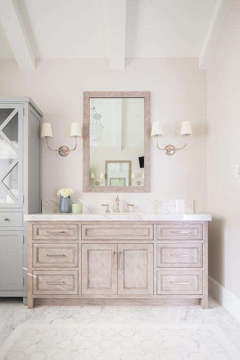 vendome double sconces flank a brushed oak vanity mirror hung above a brushed oak bath vanity accented with polished nickel pulls and a white marble