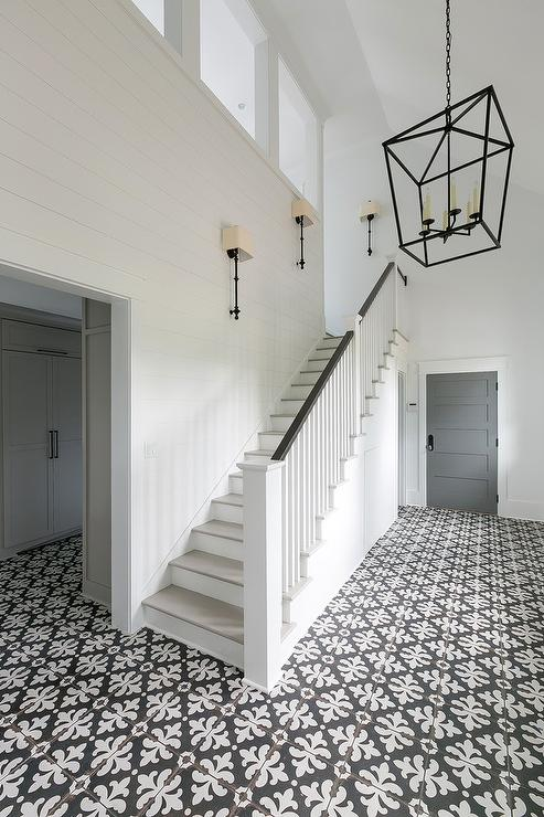 Black And White Staircase With Bronze Wall Sconces