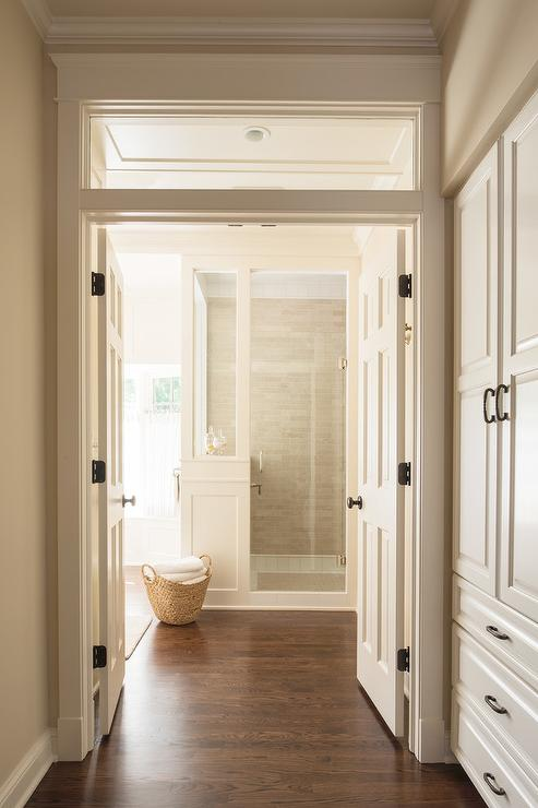 A Transom Window Is Located Above White Double Doors Opening To A Master A  Bathroom Fitted With A Wood Floor Leading To A Walk In Shower.