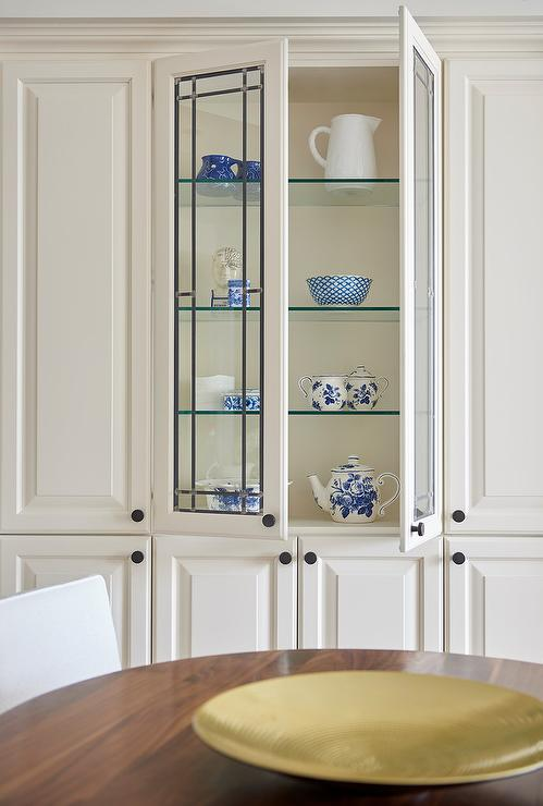 A Leaded Glass China Cabinet Fitted With Shelves Is Framed By White Floor To Ceiling Cabinets Contrasted Oil Rubbed Bronze Knobs