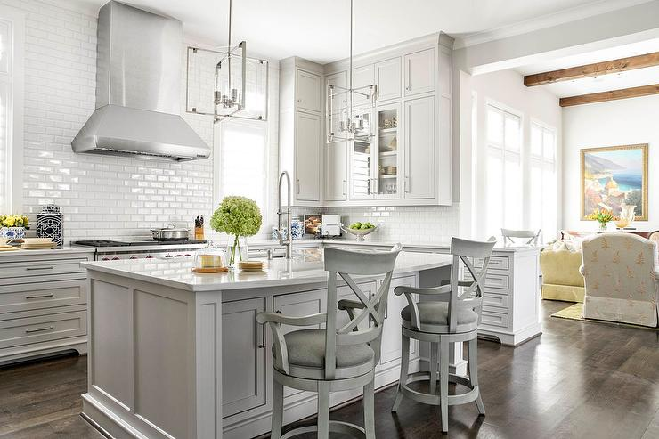 All White Kitchen With Subway Tiles Lightens Up The Room Along With Light Gray Wood X Back Counter Stools At A Center Island