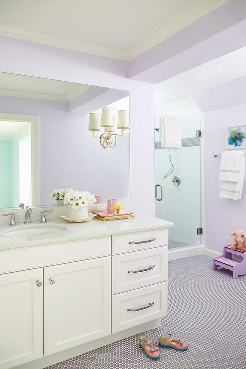 White and purple girl's bathroom is clad in purple penny floor tiles fixed framing a white washstand adorned with polished nickel hardware and a gray corian ...