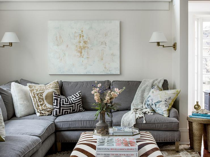 Transitional Living Room Boasting Gold Suzani Pillows On A Gray Corner Sectional Paired With Zebra Ottoman As Coffee Table
