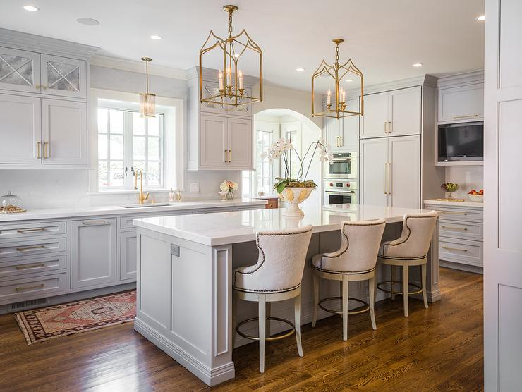 Gothic Lanterns light a light gray island topped with a white quartz countertop seating white upholstered counter stools accented with a nailhead trim. & Brass Gothic Kitchen Lanterns Design Ideas