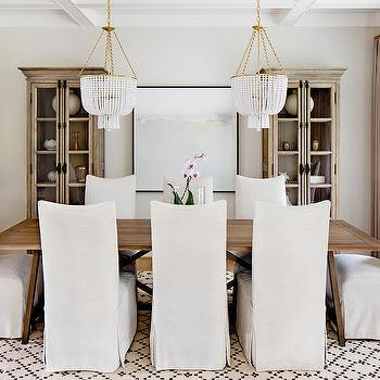 Two White Beaded Chandeliers Over Trestle Dining Table