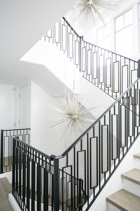 Staggered Silver Sputnik Chandeliers Illuminate A Staircase Fitted With  Gray Treads And Wrought Iron Spindles With A Wrought Iron Railing  Contrasting White ...