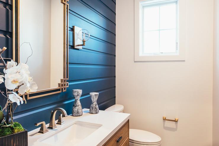Cream Stone Powder Room Wall With Round Brass Mirror