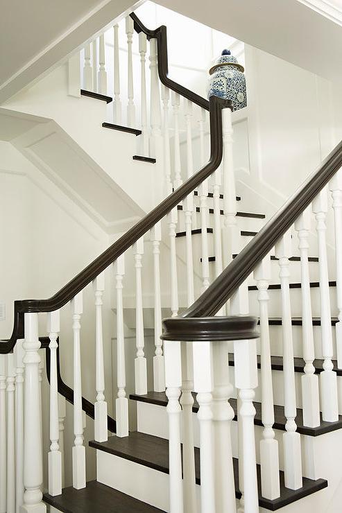A White Staircase With White Spindles Is Contrasted With Dark Brown Treads  And A Dark Brown Handrail.