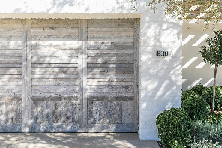 White Brick Home With Black Garage Doors Cottage Home