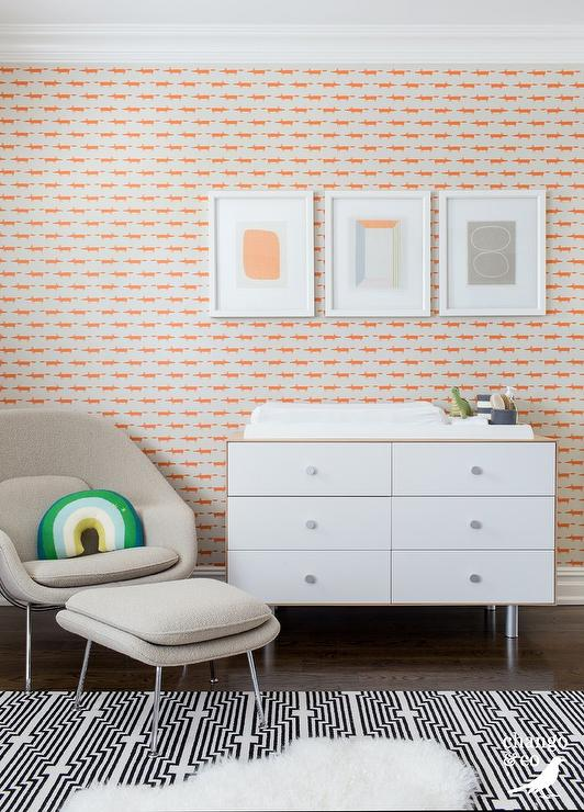 Three orange and gray abstract art pieces hang from a wall covered in Scion Spirit & Soul Little Fox Wallpaper over a two tone dresser and changing table.