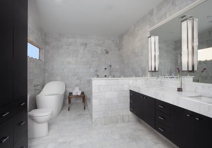 White Herringbone Tiles On Wall Behind Oval Bathtub