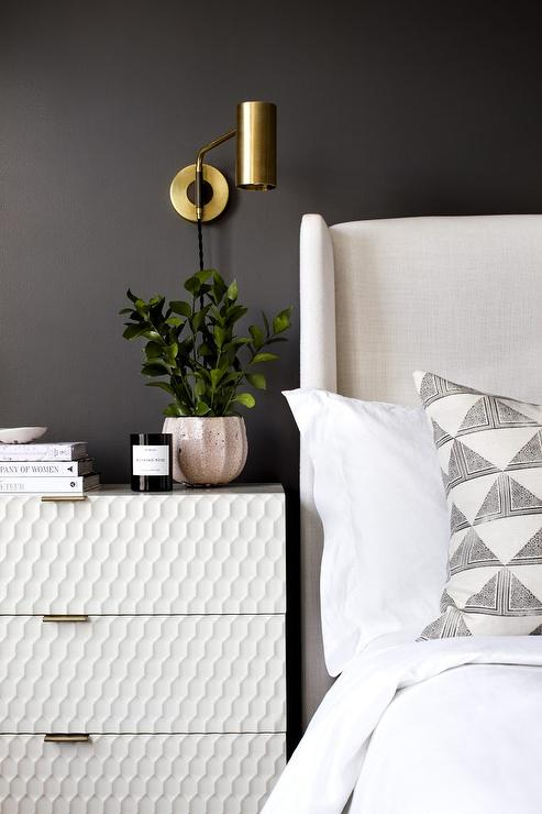 Black Bedroom Wall With White Bed And Brass Sconce
