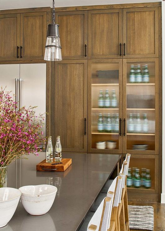 Brown Wood Kitchen Cabinets With Rippled Glass Doors Transitional