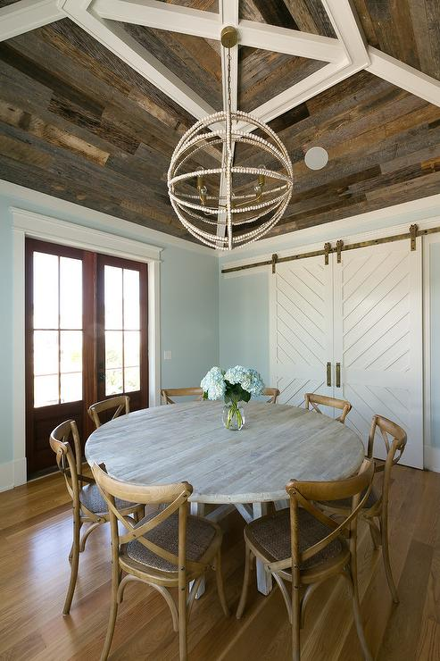 French X Back Wooden Dining Chairs Sit Around A Reclaimed Wood Dining Table  Lit By A Sphere Beaded Chandelier Hung From A Vaulted Barn Wood Ceiling  Accented ...
