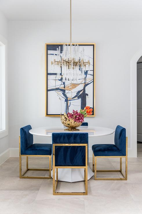 Luxe Dining Space Boasts Contemporary Furnishings A Set Of Gold And Sapphire Blue Velvet Chairs Frame Round White Table Under Brass