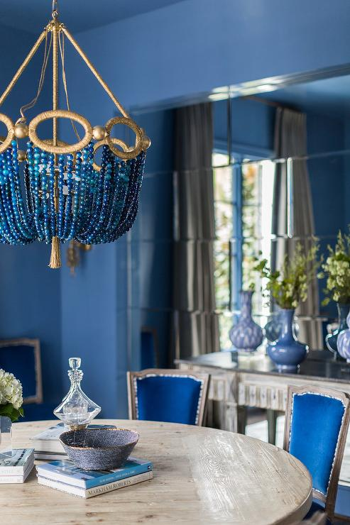 Blue Beaded Chandelier Over Round Gray Wood Dining Table