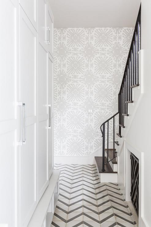 Black and white marble chevron floor tiles in a long mudroom featuring floor to ceiling cabinets and white and gray China Seas Sigourney Wallpaper.