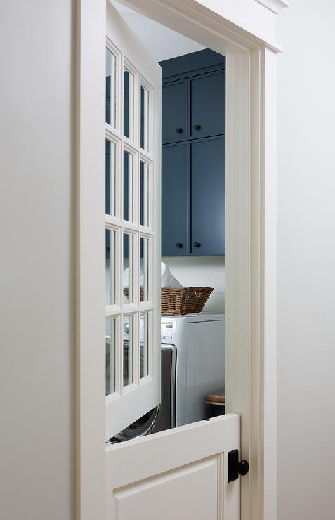 A White Dutch Door Fitted With Glass Panels And An Oil Rubbed Bronze Door  Knob Opens To A White And Blue Laundry Room Boasting Stacked Blue Flat  Front ...