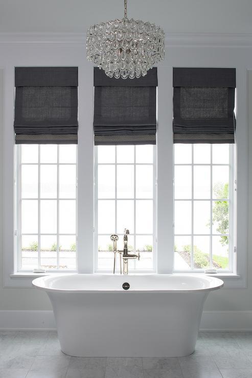 White Roll Top Bathtub Under Three Windows With Black Roman Shades Transitional Bathroom