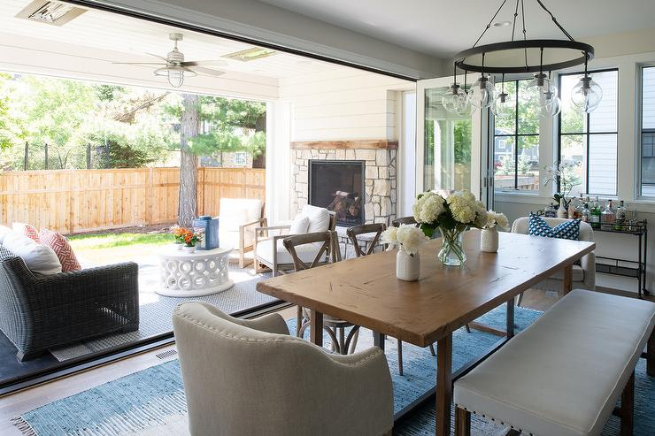 Folding Glass Patio Doors Open To A Dining Room Boasting A Wrought Iron  Candelabra Hung Over A Rustic Dining Table Placed On A Blue Wool Rug And  Seating ...