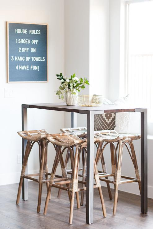 Backless Wicker Dining Stools Sit At An Industrial Pub Height Table In Front Of A Window