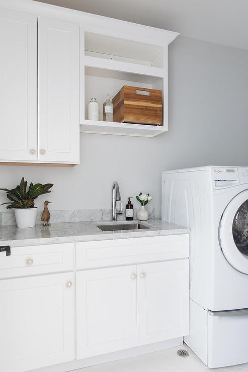 White Shaker Laundry Room Cabinets Accented With Pearlized Knobs And A  Marble Countertop Are Fitted With A Small Undermount Stainless Steel Sink  And A ...