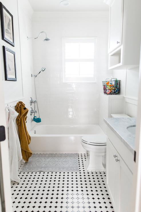 Black And White Vintage Floor Tiles Lead Past A White Washstand To A Gray  Bath Rug Placed Beneath Low Towel Hooks And In Front Of A Drop In Bathtub.