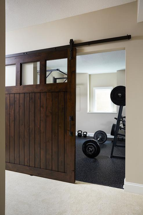 Dark brown stained barn door on rails on home gym transitional