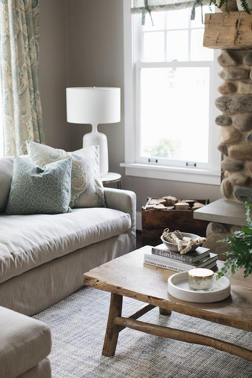 Lit By An Aerin Culloden Lamp, This Cozy Cottage Living Room Features A  Gray Linen Sofa Accented With Blue And Gray Pillows And Placed On A Gray  Rug Facing ...