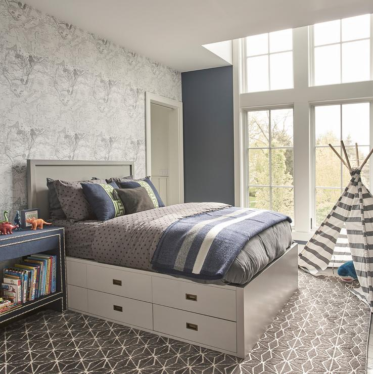 d14f71e0ebf6ca Transitional bedroom boasting a campaign platform bed with a gray wood  headboard and stacked drawers dressed in blue and gray bedding.