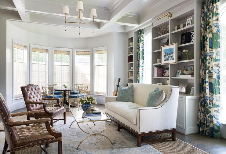 Stunning Living Room Boasts Windows Dressed In Blue And Green Curtains  Positioned Flanking Gray Built In Shelves Lit By An Antique Brass Picture  Light And ...