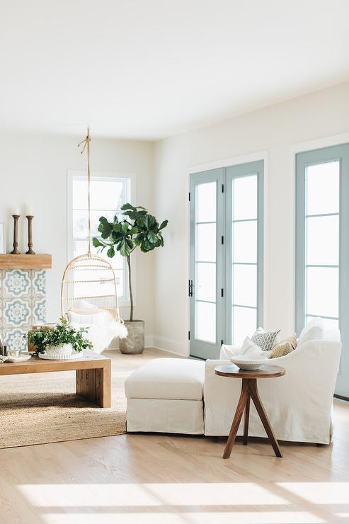 Blue French Doors Accent A Beautifully Styled Living Room Featuring A White  Slipcovered Chair Placed Beside A Round Wood Accent Table.