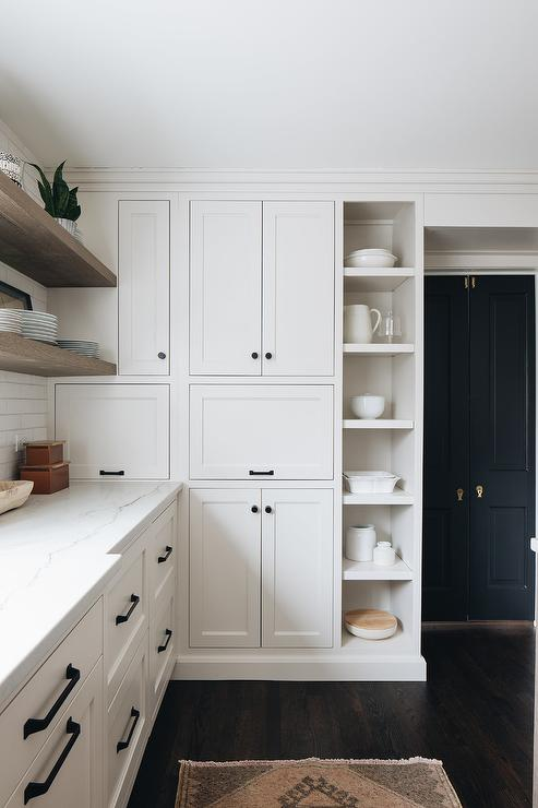Stacked White Shaker Kitchen Cabinets Accented With Oil Rubbed Bronze  Hardware Are Finished With Vertical Display Shelves.