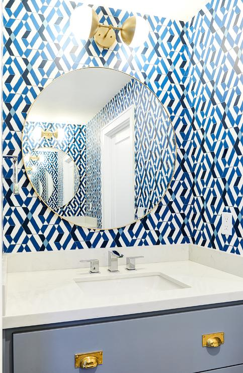 A Brass 2 Light Sconce Is Mounted To White And Blue Geometric Backsplash  Tiles Over A Round Brass Vanity Mirror Fitted In A Boyu0027s Bathroom Over A  Gray ...