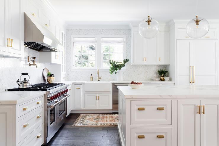 white kitchen cabinets with bronze hardware White Kitchen With Brushed Gold Cup Pulls Transitional